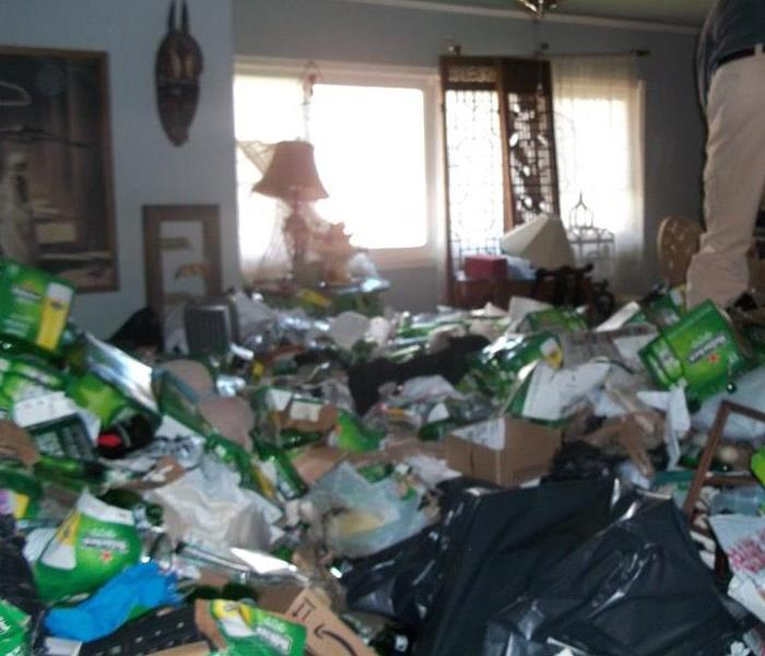 Living room covered in various pieces of trash