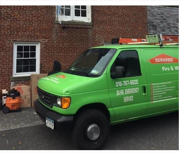 green van, brick building behind, ladders on vehicle