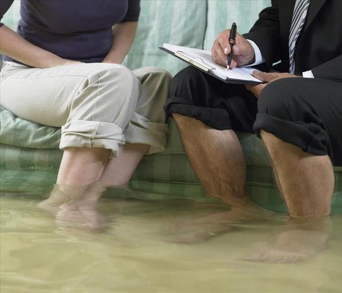 man and woman on couch pants up to their knees feet in living room water discussing flood damage